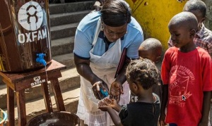 Community health worker Marrion Thomson teaches children how to wash their hands