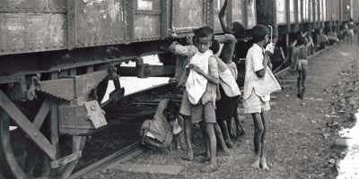 Children trying to pierce bags of grain in stationary train carriages, Bengal, 1943