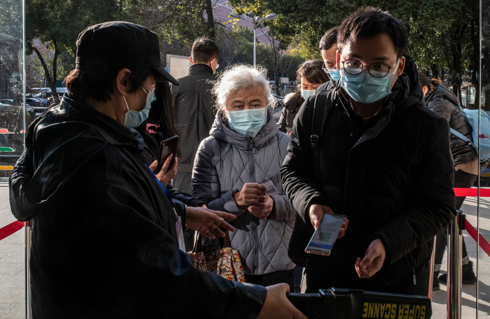 At the entrance of Zhongnan Hospital in Wuhan, an employee asks a visitor to scan a code that allows for a health check.
